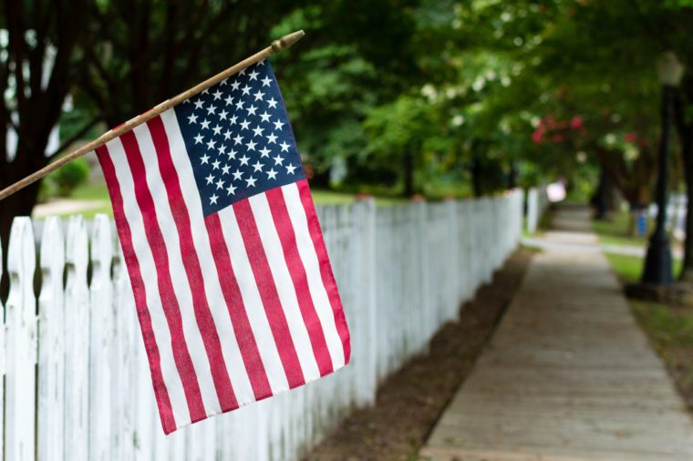 Small American flag hangs from a picket fence along the sidewalk in a rural town.