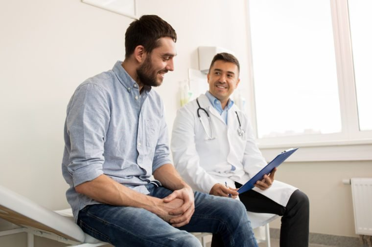 medicine, healthcare and people concept - smiling doctor with clipboard and young man patient meeting at hospital