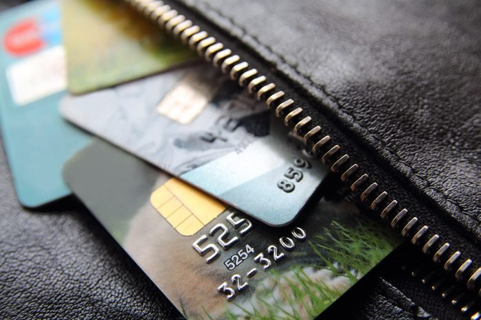 Credit cards peeking out of the black leather bag or purse, close-up.