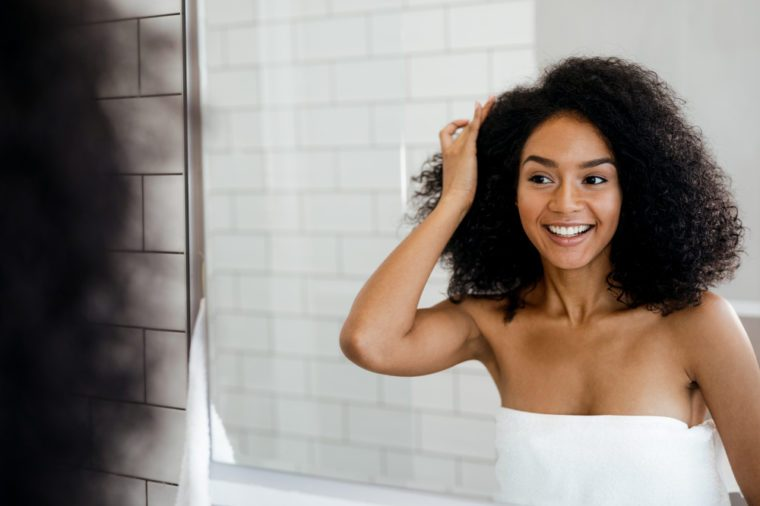 Young smiling woman examining her hair in the bathroom, looking into a mirror