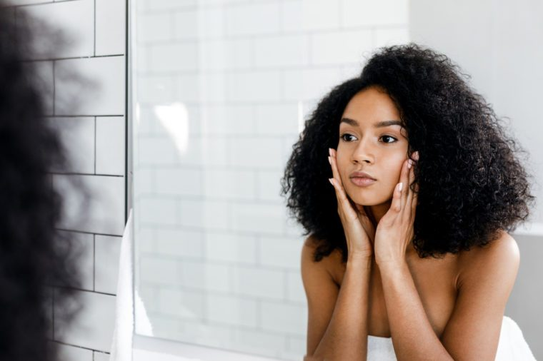 Mixed race woman massaging her face and looking at a mirror