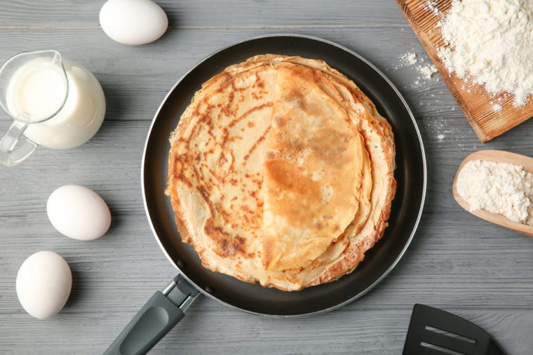 Pan with delicious thin pancakes on wooden table