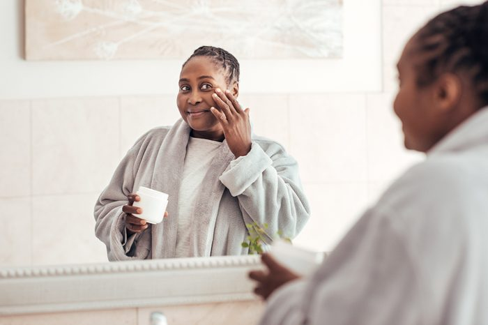 Smiling young African woman wearing a robe standing in her bathroom in the morning applying moisturizer to her cheek in a mirror