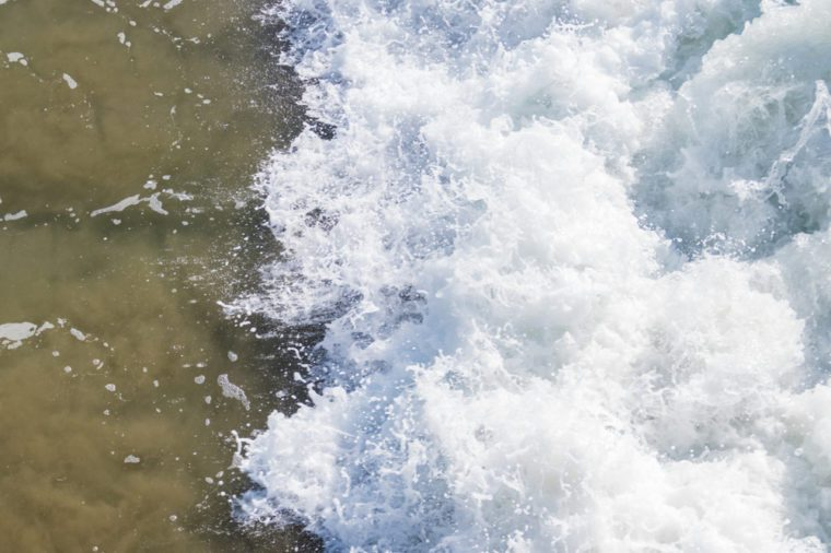textured overhead view of wave crashing into shoreline