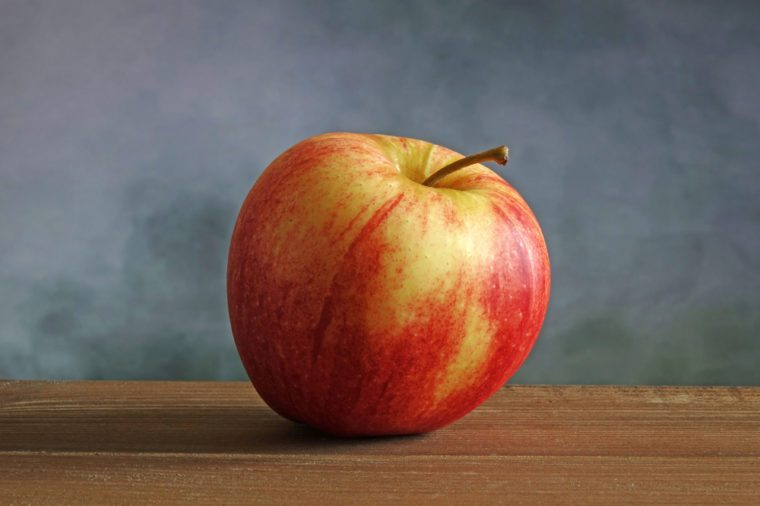 Organic Gala apple on wood table. Selective focus, blurred concrete wall background.