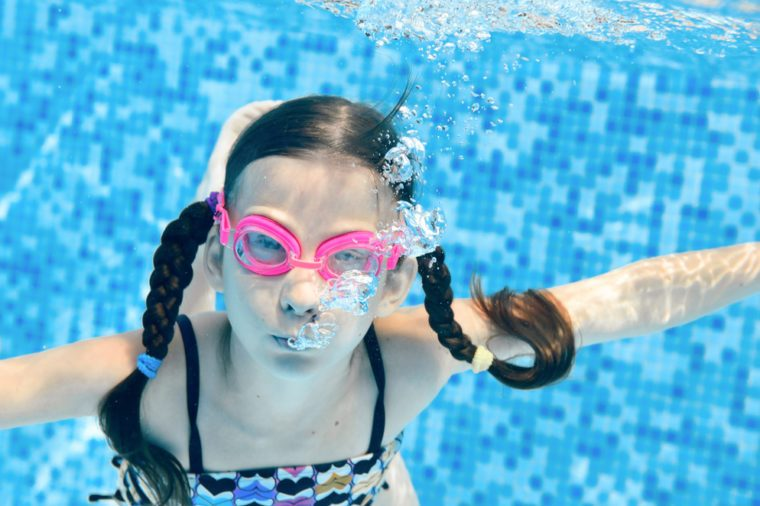 Child swims in swimming pool underwater, happy active girl dives and has fun under water, kid fitness and sport on family vacation