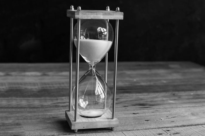 Hourglass or vintage sandglass on wooden background (selective focus)