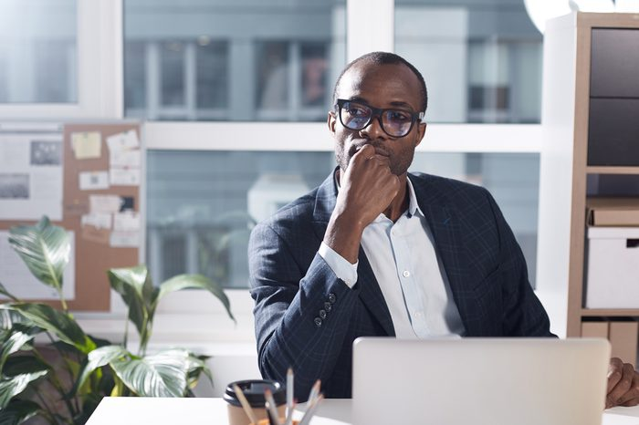 Dreaming about future. Portrait of calm pleasant young african manager in glasses is sitting at table with laptop and touching his chin while looking aside wistfully. Copy space in the left side