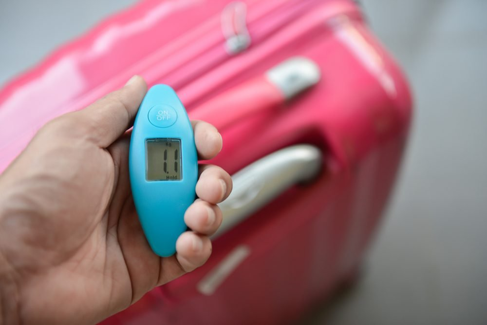 Man hand is using digital weight scale baggage