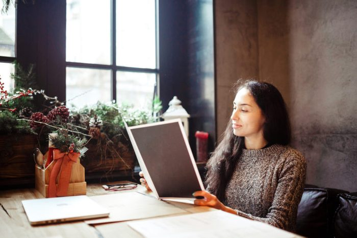 young business girl studying the menu in restaurant decorated with Christmas decor.sits near the window on cloudy winter day at wooden table.Dressed in warm gray sweater.On the table,phone and glasses