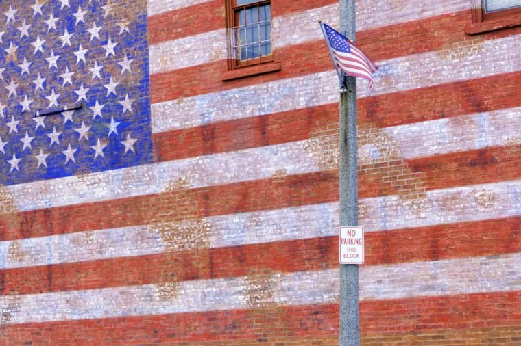 Small-town street scene in Illinois: American flag flapping in breeze by huge painted American flag fading from brick wall