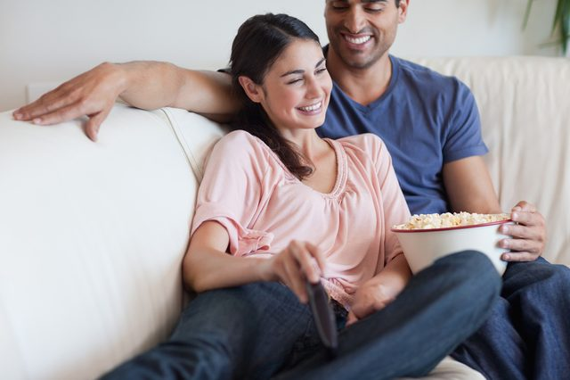 Delighted couple watching TV while eating popcorn in their living room