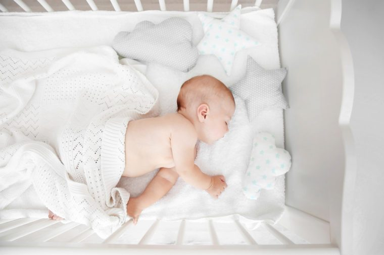 Little baby sleeping in crib , top view