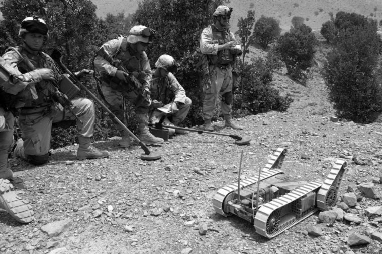 """SOLDIERS MANEUVER ROBOT Land mine detectors stand by as a U.S. army soldier maneuvers """"Hermes"""" the robot into a cave to detect mines, traps, and other unexploded ordinance as well as weapons or equipment possibly hidden by Taliban or al-Qaida fugitives in the eastern border town of Qiqay, Afghanistan, . The current war in Afghanistan marks the first use of the robots by conventional military forces in combat situations with hopes to prevent unnecessary casualties"""