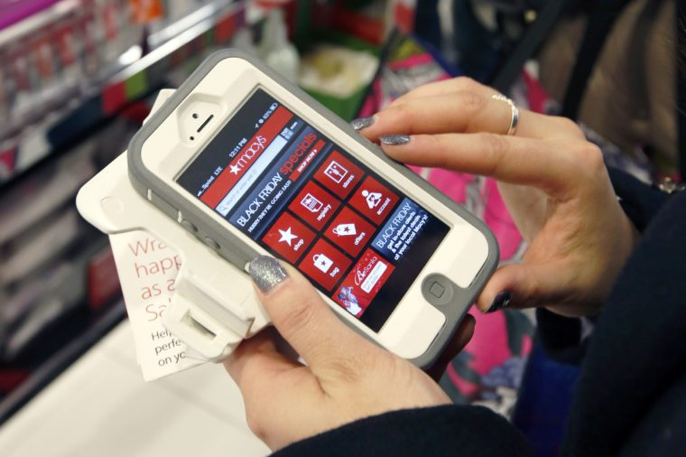 Tashalee Rodriguez, of Boston, uses her smartphone while shopping at Macy's in downtown Boston. Facebook isn't just for goofy pictures and silly chatter. Whether shoppers know it or not, their actions online help dictate what's in stores during this holiday season