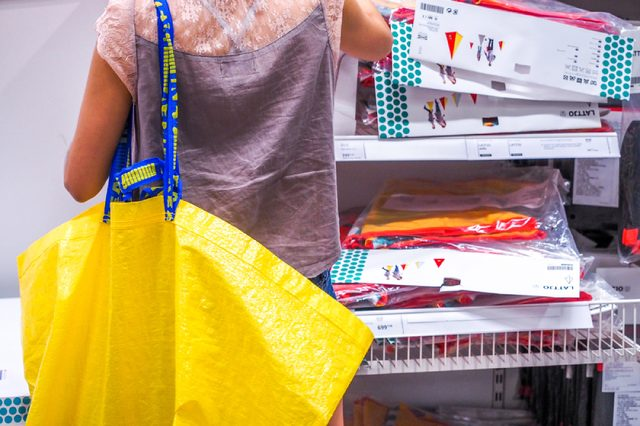 The woman shopping with Big yellow shopping bags in IKEA Store. IKEA is the world's largest furniture retailer, founded in Sweden in 1943