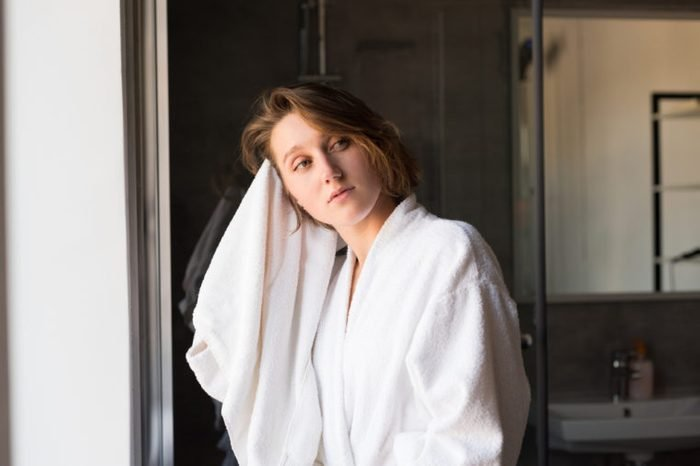 pensive young woman in bathrobe drying hair with towel in bathroom