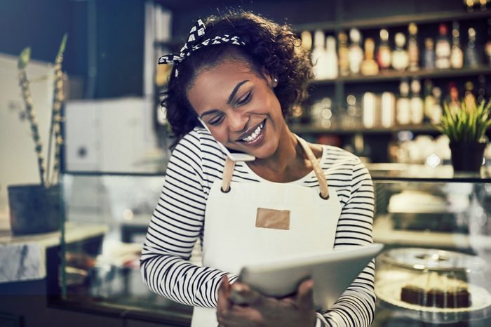 Smiling young African entrepreneur standing at the counter of her cafe talking on a cellphone and using a tablet