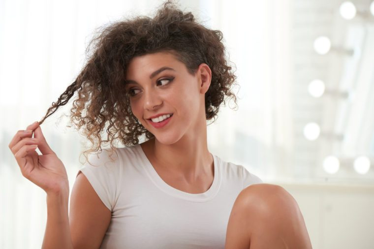 Smiling young woman looking at her curly hair
