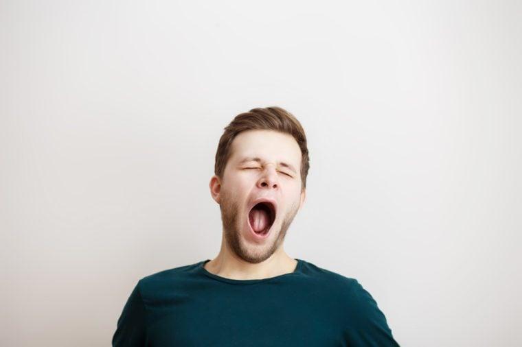 Portrait of yawning man on a light background