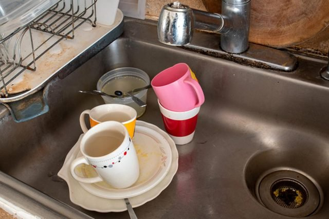 Dirty dishes and glasses water in kitchen sink
