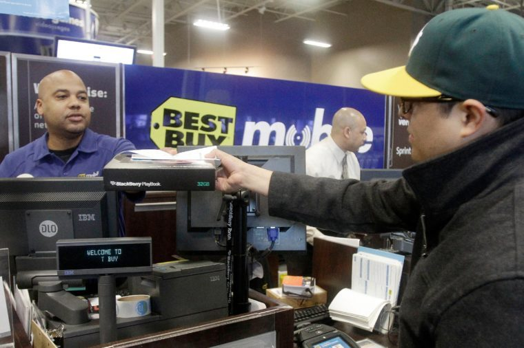 Mikel Calderon, right, buys a BlackBerry PlayBook tablet at a Best Buy store in San Francisco