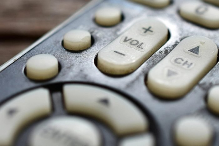 A low angle close up view of a TV remote control on a wooden table.