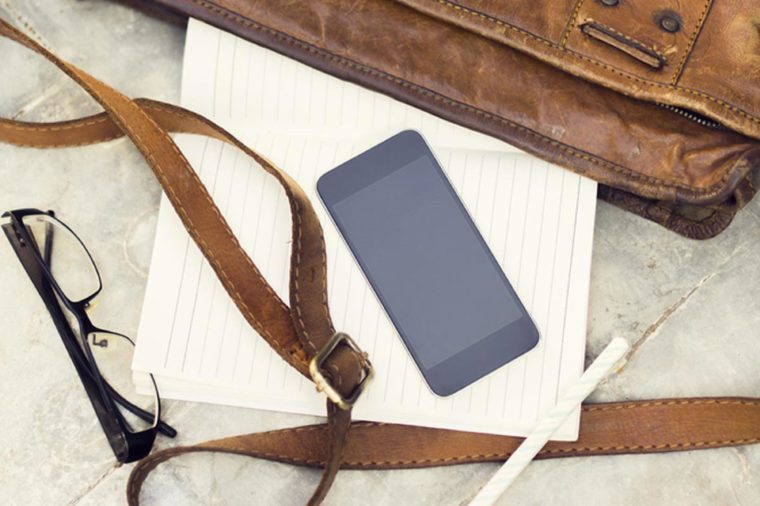 brown leather handbag, blank cell phone, diary and glasses
