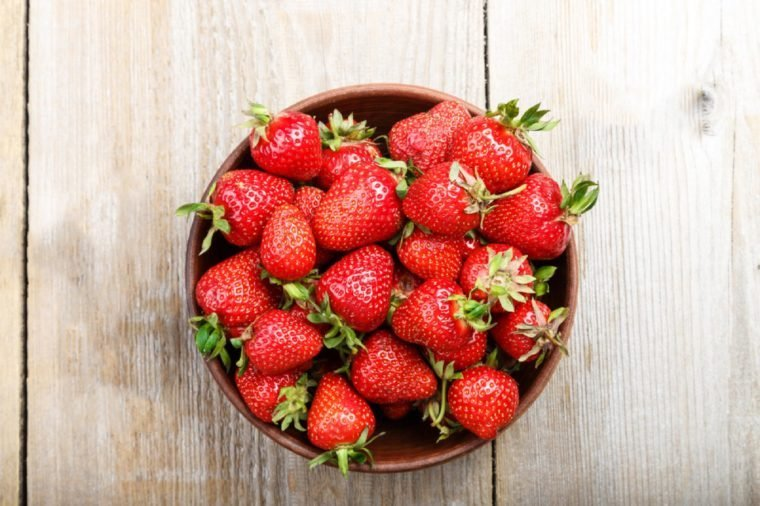 Fresh strawberry in a clay plate on wooden table , top view
