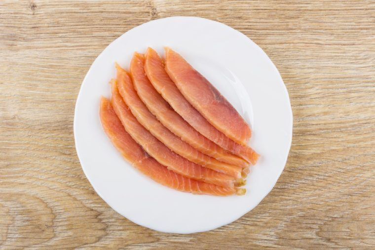 Slices of salted salmon in white plate on wooden table. Top view