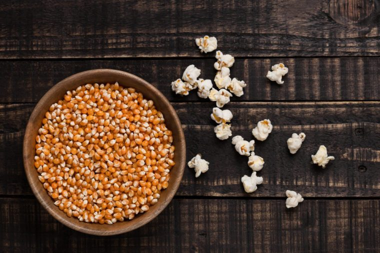 Wooden bowl with raw sweet corn and popcorn on wooden background
