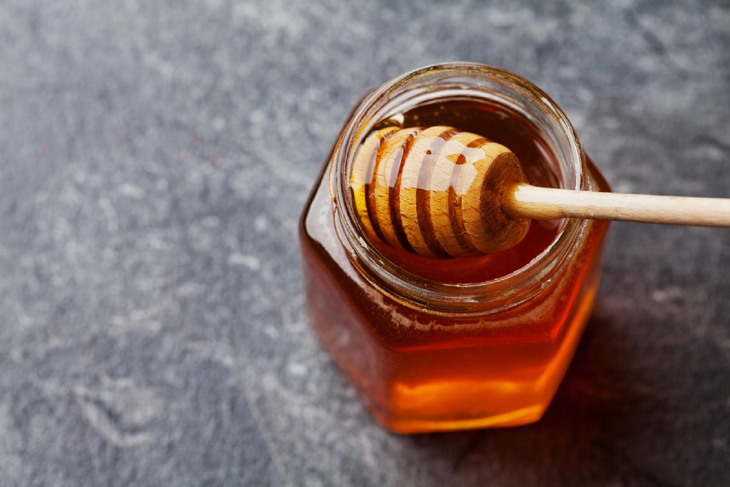 Honey in a pot or jar on kitchen table, top view