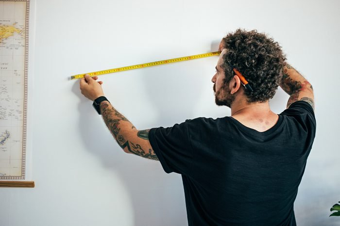 Hipster millennial man with arm tattoos and curly hair, small business owner, contractor measures wall to start reconstruction or adapt for painting, new home ownership