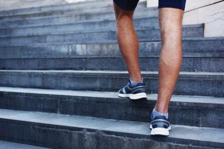 Sport, fitness and healthy lifestyle concept - man running in the city, feet of male runner on steps of stairs closeup over urban background