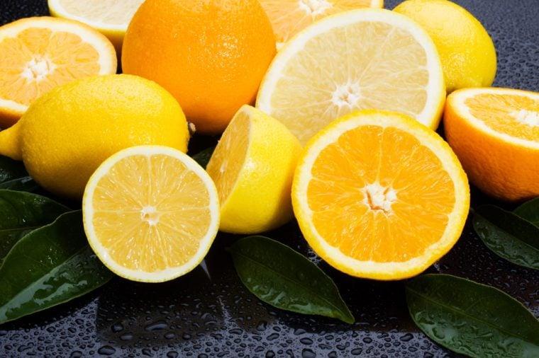 Lemon, orange and grapefruit on wet background