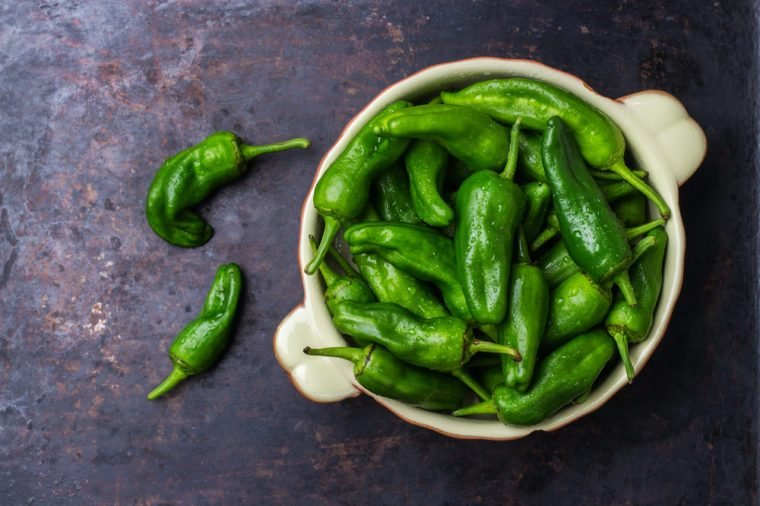Food and drink, still life concept. Raw green peppers pimientos de padron mexican jalapeno traditional spanish tapas on a table. Selective focus, top view flat lay overhead