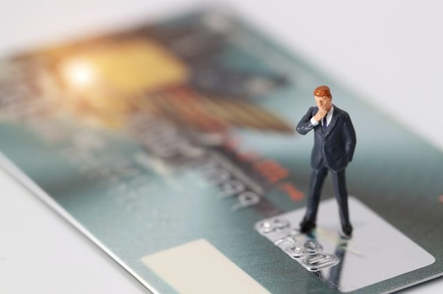 Miniature people: businessman standing and thinking of something on credit card as payment and purchase online solution (e-commerce and shopping concept)