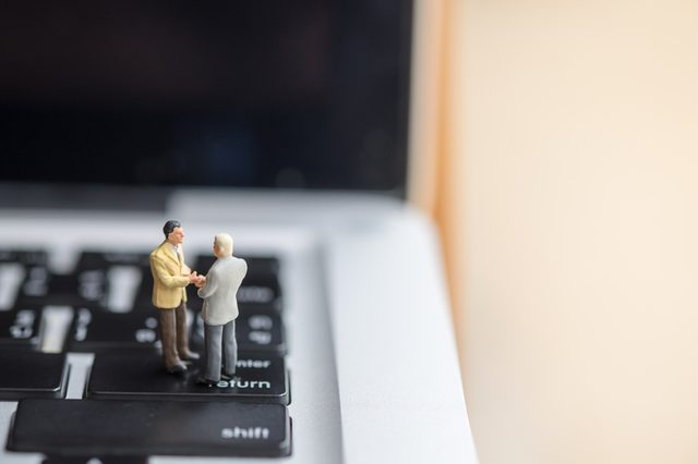 Business and computer Concept. Two businessman miniature figures handshake on laptop computer.