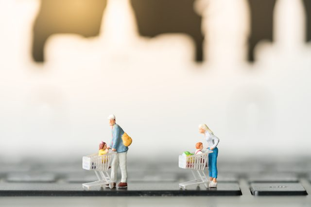 Miniature with shopping cart using as background business online concept.
