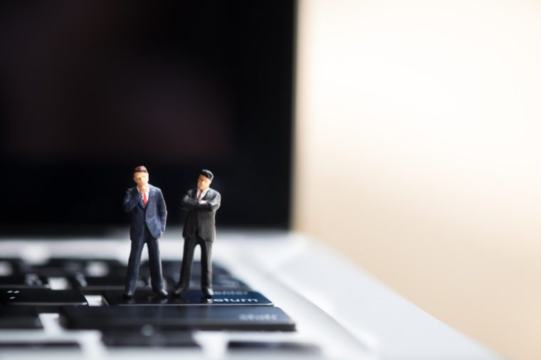 Business and technology concept. Two businessman miniature figures standing on enter / return button of laptop computer with copyspace for text.