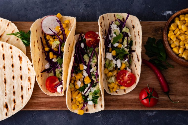 Pulled pork tacos with red cabbage, tomatoes, corn, feta and avocados overhead shot.