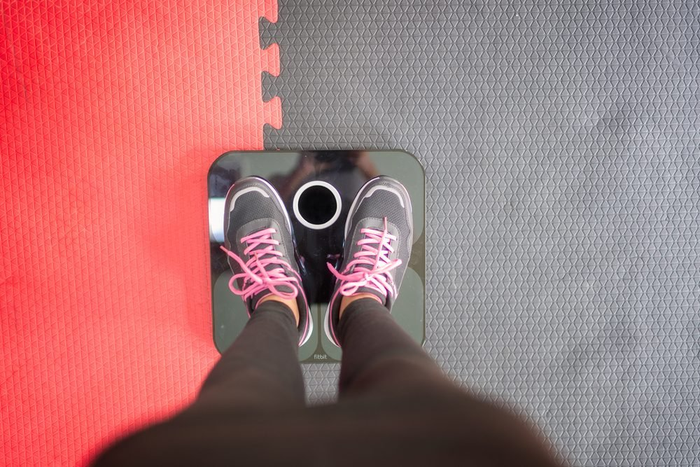Woman standing on weigh scales at gym.Waist measurement by tape measure .Concept of healthy lifestyle.