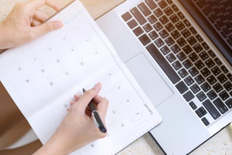 Businesswoman planning agenda and schedule using calendar event planner. Woman hands writing plan for working and schedule this month. Planner of meeting plan job.