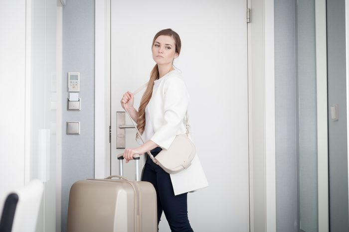 Young sad woman pulling suitcase and leaves modern hotel room