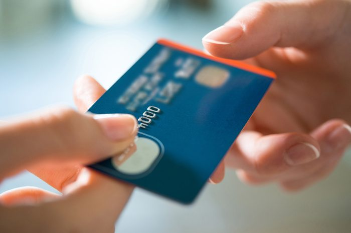 Closeup shot of a woman passing a payment credit card to the seller. Girl holding a credit card. Shallow depth of field with focus on the credit card.