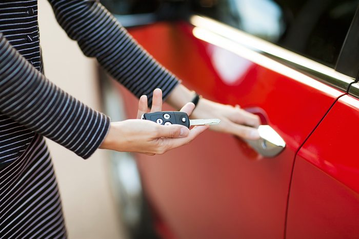Beautiful young girl with car key in hand and opens the car