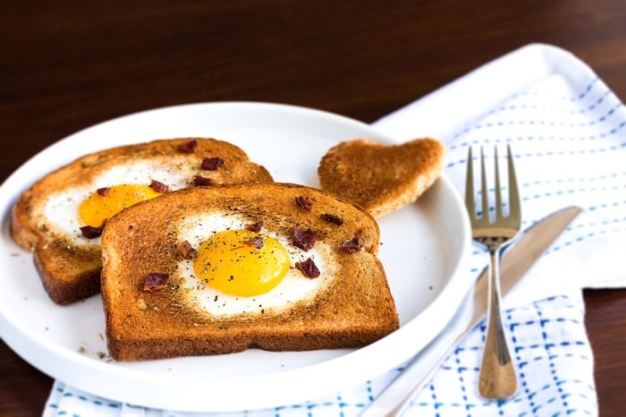 Egg fried in a heart-shaped toast cutout sprinkled with bacon crumbs, cracked pepper and thyme