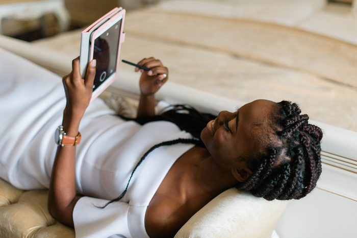 african woman on the sofa and using her tablet. Vip hotel