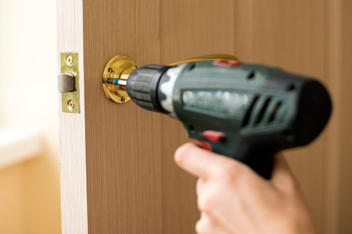 Installation of door lock using a screwdriver to. Carpenter at lock installation with electric drill into wood door. Installation lock. Carpenter installation. electric drill. screwdriver