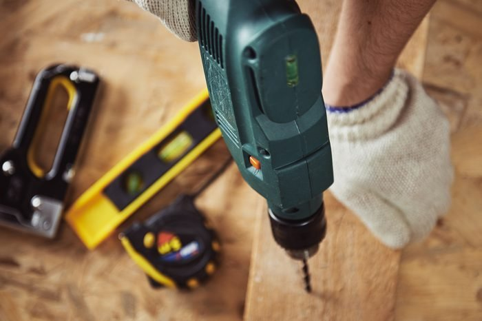 Building master with drilling machine. Professional carpenter working with wood and building tools in house.